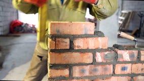 bricklaying Hände, die einen Ziegelstein auf eine Baustelle setzten stock video footage