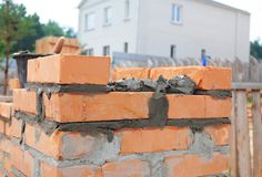 Bricklaying house brick wall. Close up on laying bricks with concrete stock image