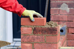 Bricklaying - laying a brick Stock Image