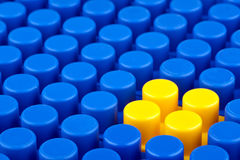 Bricks. In the picture a bunch of blue plastic blocks and one yellow. They are not legos Stock Photos
