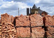 Bricks. Stacked bricks and built house on the background royalty free stock photos