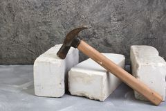 Silicate bricks, hammer on the gray concrete background. Copy space. Top view. stock images