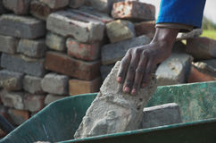 Bricks, hands and wheelbarrow Stock Photos