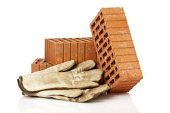 Bricks and protective gloves isolated on white Stock Photos