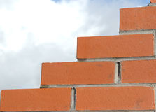 Bricks and sky. Red bricks constructed into a wall with cement pointing and a stepped jagged edge against a cloudy sky Royalty Free Stock Photos