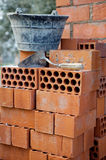 Bricks stacked, trowel and cube in the work Stock Photos