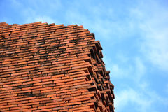 Ancient bricks from a part of a wall standing out in a bright blue cloudy sky Stock Photos