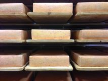 Bricks of Swiss cheese aging on wooden shelves. At a cheesemaker's, bricks of Swiss cheese rest on wooden shelves to age before they can be sliced and sold Stock Photo