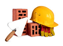 Bricks, trowel and helmet on isolated background Royalty Free Stock Photos