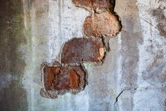 Bricks visible in the split plaster of the old wall Royalty Free Stock Images