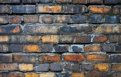 Bricks in the Wall. Weather-beaten bricks show their age as its deteriorating mortar falls away. soot adds flavor to the multi colored and stained brickwall as Stock Photo