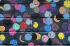 Bricks wall is decorated with bright abstract colored circles on black background closeup. Detail like as graffiti. Bricks wall is decorated with bright abstract royalty free stock images