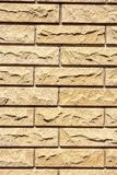 Bricks in the wall. Fragment of the wall, composed of light uneven bricks, vertical shot stock photo