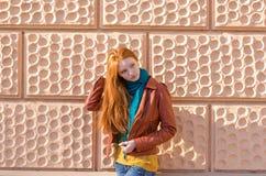 摆在桃红色brickwall前面的可爱的小姐 免版税库存照片