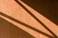 Brickwall with light pattern. Brickwall with a light pattern, shadows top and bottom light from upper left to lower right royalty free stock photos
