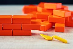Brickwork from toy blocks and a trowel. Unfinished construction concept. Brickwork from toy blocks and trowel. Unfinished construction concept stock photos