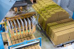 Brickyard. Top view of stacked bricks in workshop. Brickyard. Top view of machine and stacked bricks in workshop royalty free stock photos