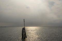 Bricole di legno con illuminazione pubblica nel mare sulla direzione da Chioggia a Venezia, Italia fotografia stock