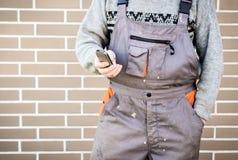 Bricoleur anonyme avec le téléphone portable, 24/7 concept d'aide Photographie stock libre de droits