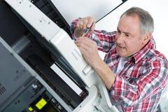 Bricoleur de bureau ayant la difficulté réparant l'imprimante images stock