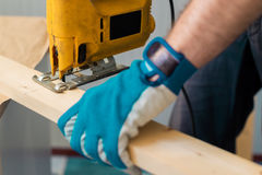 Bricoleur de charpentier à l'aide de la scie pratique électrique Photographie stock