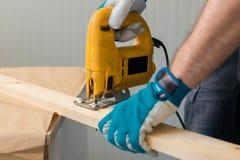 Bricoleur de charpentier à l'aide de la scie pratique électrique Photographie stock libre de droits