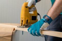 Bricoleur de charpentier à l'aide de la scie pratique électrique Photos libres de droits