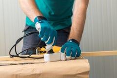 Bricoleur de charpentier branchant la scie pratique électrique Image stock
