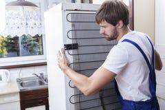 Bricoleur essayant de déplacer un réfrigérateur image libre de droits