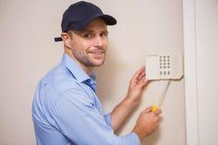 Bricoleur fixant un système d'alarme photo stock