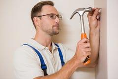 Bricoleur martelant le clou dans le mur Image stock