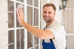 Bricoleur nettoyant la fenêtre et le sourire photo libre de droits