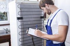 Bricoleur pendant la réparation de réfrigérateur photographie stock libre de droits