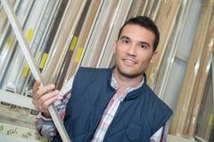 Bricoleur sélectionnant le bois de construction du support dans le matériel image stock