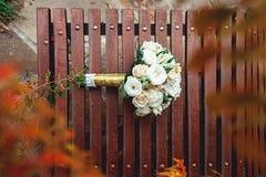 Bridal букет белых роз с лентой золота на коричневом стенде Стоковые Фотографии RF