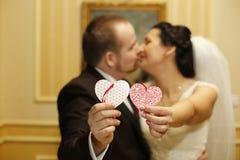 Bridal пары держа 2 бумажных сердца Стоковое Фото