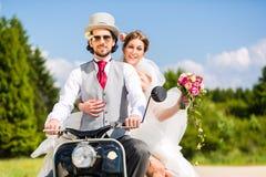 Bridal пары управляя мантией и костюмом мотороллера нося Стоковое Фото