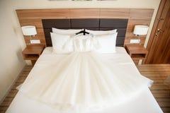 Bridal шикарное платье на кровати Стоковые Изображения