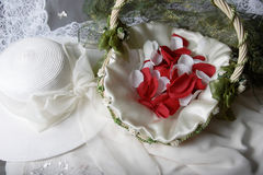 Bridal accessories. Bridal hat beside a basket of rose petals Stock Photo