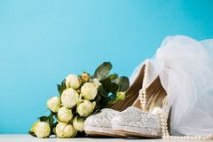 Bridal accessories composed together on blue. Lace high heels and pearl necklace arranged with bouquet and veil on blue studio background royalty free stock photography