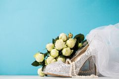Bridal accessories composed together on blue. Lace high heels and pearl necklace arranged with bouquet and veil on blue studio background royalty free stock image