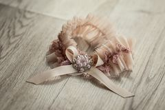 Bridal accessories such as wedding garter lie on a table stock image