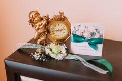 Bridal accessories on table with golden vintage looking clock Stock Image