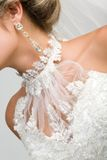 Bridal attributes. Close-up of bridal neck and chest framed by white wedlock lace and with elegant earring in ear Royalty Free Stock Image