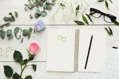 Bridal background with planner checklist. Wedding background with checklist. Paper planner and wedding rings on white wooden table with lots of tender bridal Stock Image