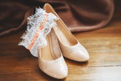 Bridal beige wedding shoes with garter, wooden background. Marriage concept. Bridal beige wedding shoes with garter on wooden background. Marriage concept Royalty Free Stock Photos