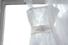 Bridal Bling. Elegant window dressing bedazzles the frame with sequins, bling and an ivory sash. Bridal gown hands from window facing stock images