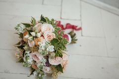 Bouquet for the bride. A bridal bouquet for the bride of spray roses, matiolla, greenery of pitosporum, limonium and sedum lies on the white wooden floor stock photos
