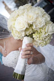 Bridal Bouquet. Vertical image of a bride holding her bouquet made of white roses royalty free stock photography