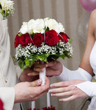 Bridal Bouquet. Bridegroom giving wedding bouquet to his bride, red and white roses and babies breath Royalty Free Stock Photos